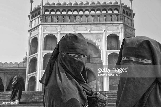 Veiled ladies close up one walks up stairs in background to MOSQUE in Bhopal INDIA