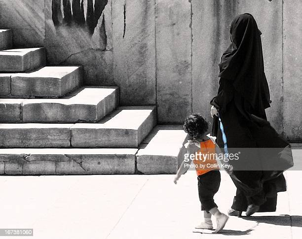 Veiled mother walk her daughter on a leash