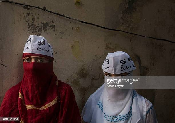Veiled Muslim supporters of AAP leader Arvind Kejriwal wait for his convoy to pass during a rally by the leader on May 9 2014 in Varanasi India India...