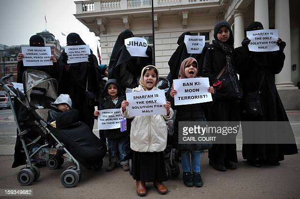 Veiled Muslim women and children hold up signs reading 'Jihad' and calling for Shari'ah law in Mali as they protest in response to French military...