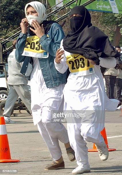 Veiled Pakistani female athletes run during the short version of 6 kilometers International Marathon in Lahore, 30 January 2005. Some 2,000...