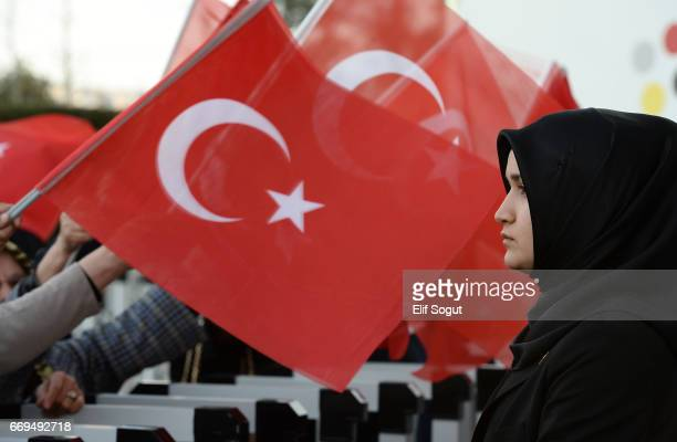 A veiled police officer stands guard during a rally by supporters of Turkey's President Recep Tayyip Erdogan at the Presidential Palace on April 17...