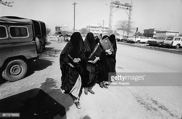 Veiled school girls wearing chadors walk home down a city street in Jiddah after their studies