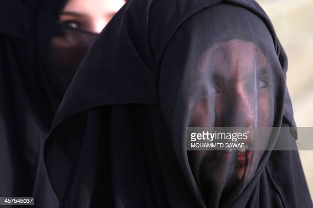 A veiled Shiite Muslim pilgrim looks over as makes her way along the main Basra highway slowly heading to the central shrine city of Karbala on...