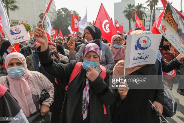 Veiled supporters wave fags of Tunisia and flags of Ennahda during a demonstration held by the Islamist party of Ennahda on Avenue Mohammed V in the...