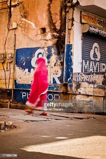 veiled woman entering alley - merten snijders stock-fotos und bilder