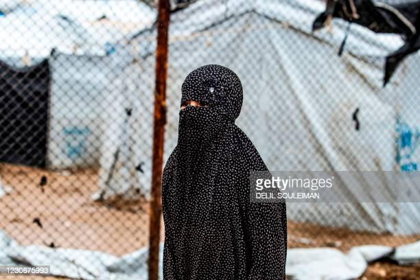 Veiled woman looks on during the release of persons suspected of being related to Islamic State group fighters from the Kurdish-run al-Hol camp in...