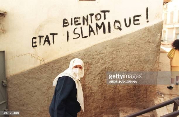 A veiled woman passes by a graffiti reading 'Soon the Islamic state' on a wall of Algiers' Casbah February 11 1992 one day after the slaying of six...