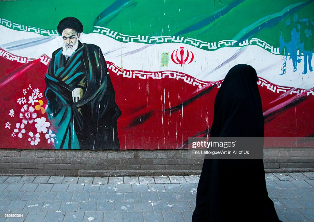 Veiled Woman Passing In Front Of Propaganda Sign With Ayatollah Khomeini On The Wall Of The Former U.s. Embassy, Central District, Tehran, Iran : News Photo