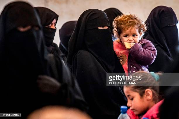 Veiled woman stands carrying a child alongside others during the release of persons suspected of being related to Islamic State group fighters from...
