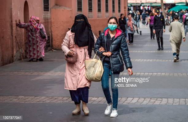 Veiled woman walks alongside another one wearing a protective mask at Marrakesh's Jamaa el-Fna square on March 16, 2020. - Many holiday makers who...