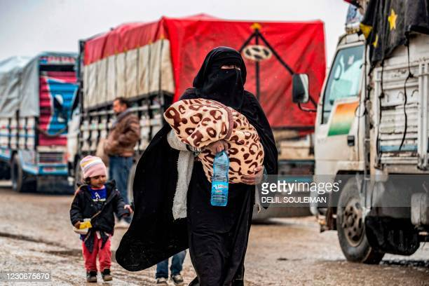 Veiled woman walks carrying wrapped a blanket during the release of persons suspected of being related to Islamic State group fighters from the...