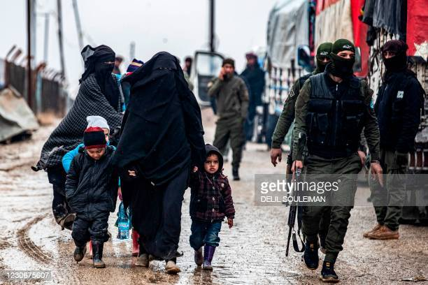 Veiled woman walks with children next to a member of the Syrian Kurdish internal security services known as Asayish, during the release of persons...