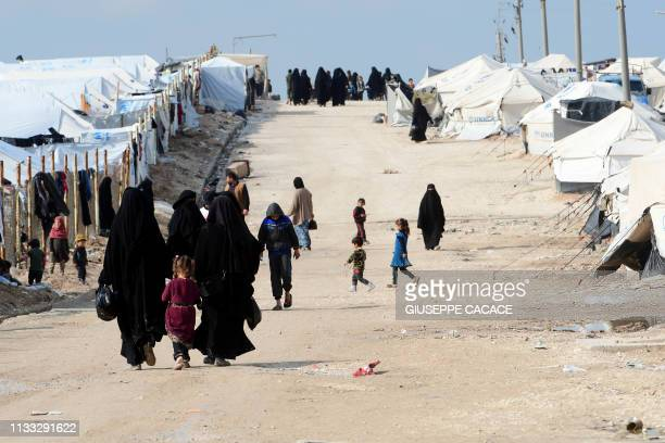 Veiled women living in alHol camp which houses relatives of Islamic State group members walk in the camp in alHasakeh governorate in northeastern...
