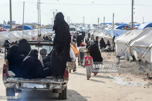 Veiled women living in alHol camp which houses relatives of Islamic State group members ride on a pickup truck in the camp in alHasakeh governorate...