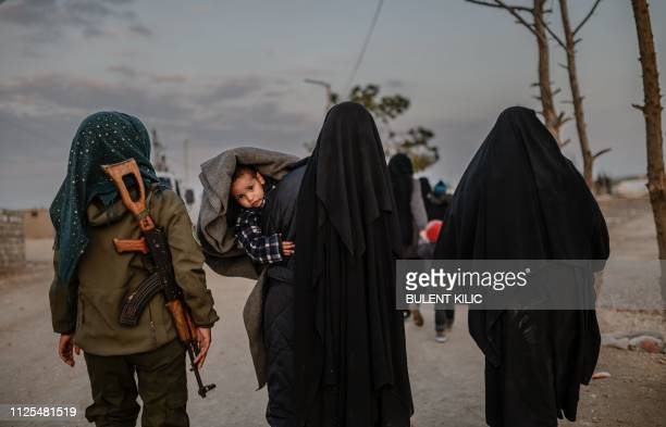 TOPSHOT Veiled women reportedly wives and members of the Islamic State walk under the supervision of a female fighter from the Syrian Democratic...