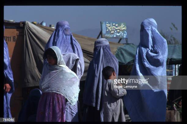 Veiled women stand in the street October 11 1996 in Kabul Afghanistan The Taliban army faces opposition by the guerrillas of Ahmas Shah Masoud allies...
