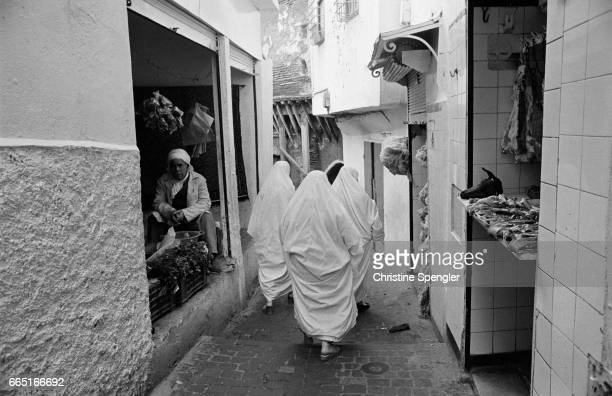 Veiled women walk down an alleyway in a street in the Casbah of Algiers