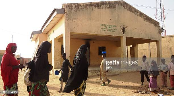 Veiled women walk past the Haye dispensary on February 8 2013 in the northern Nigerian city of Kano where gunmen on motorised tricycle killed seven...
