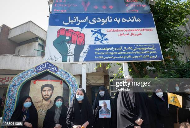 Veiled women wearing protective face masks hold a Lebanon Hezbollahs flag and a portrait of the Iranian former Islamic Revolutionary Guard Corps Quds...