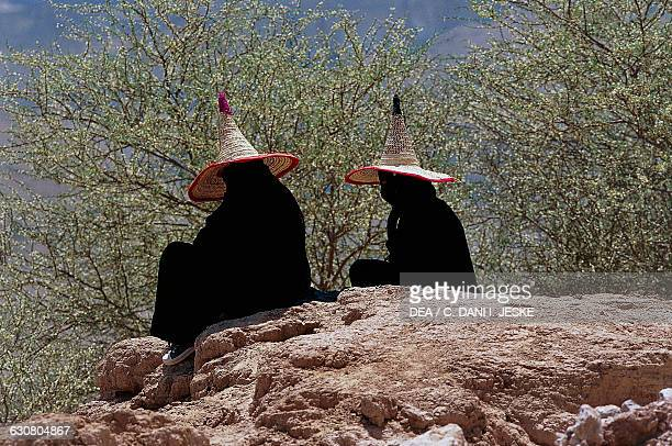 Veiled women wearing the traditional pointed hat known as the madhalla Wadi Hadhramaut Hadhramaut Province Yemen