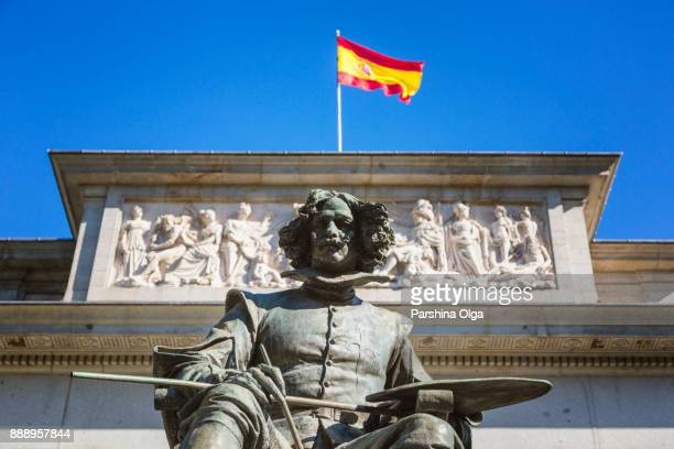 velazquez statue with flag of spain. madrid - prado stock photos and pictures