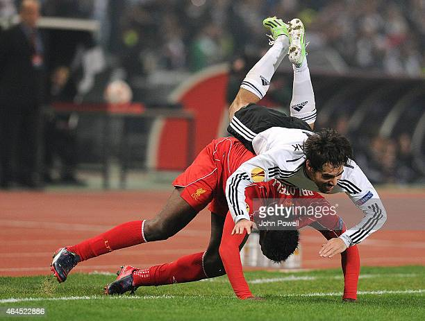 Veli Kavlak of Besiktas JK falls over Mario Balotelli of Liverpool during the UEFA Europa League Round of 32 match between Besiktas JK and Liverpool...