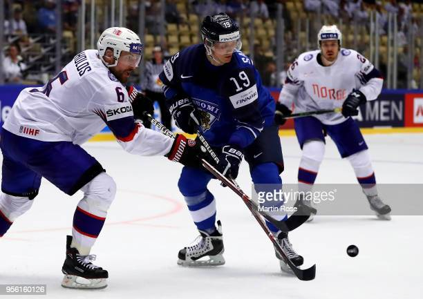Veli Matti Savinainen of Finland and Jonas Holos of Norway battle for the puck during the 2018 IIHF Ice Hockey World Championship group stage game...