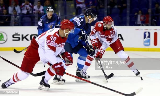 Veli Matti Savinainen of Finland challenges Markus Lauridsen of Denmark during the 2019 IIHF Ice Hockey World Championship Slovakia group A game...