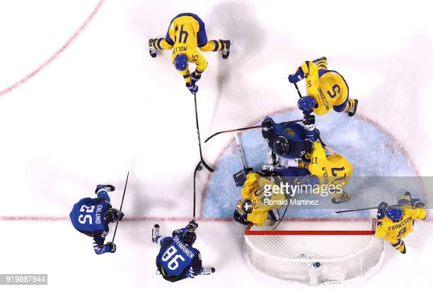 Veli-Matti Savinainen of Finland attempts a shot against Oscar Moller and goalie Viktor Fasth of Sweden in the third period during the Men's Ice...
