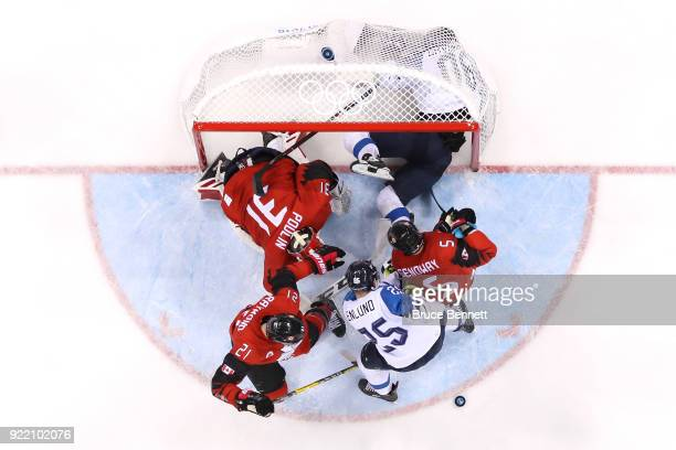 Veli-Matti Savinainen of Finland crashes in to the net in the third period against Kevin Poulin of Canada during the Men's Play-offs Quarterfinals on...