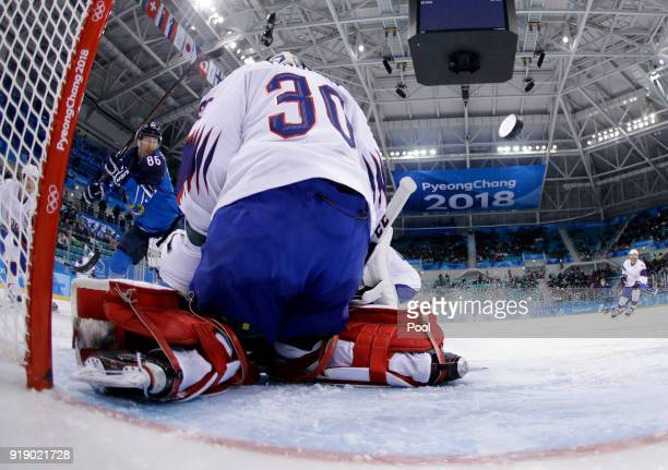 Veli-Matti Savinainen, of Finland, shoots as the puck sails past goalie Lars Haugen, of Norway, for a goal during the third period of the preliminary...