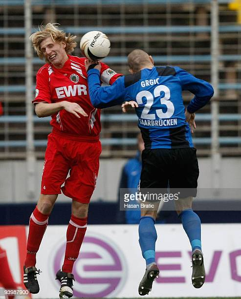 Velimir Grgic of Saarbruecken and Mathias Lang of Worms jump for a header during the Regionalliga match between 1 FC Saarbruecken and Wormatia Worms...