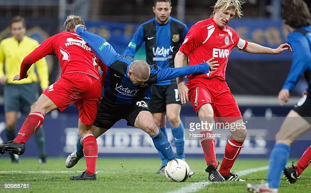 Velimir Grgic of Saarbruecken battles for the ball with Artur Krettek of Worms as well as Matthias Lang of Worms during the Regionalliga match...