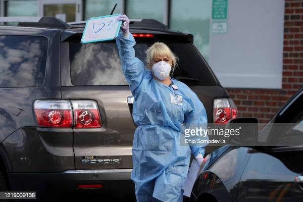 Velocity Urgent Care operations coordinator and medical assistant Lucy Adkinson holds up a sign while looking for the next patient to test for the...