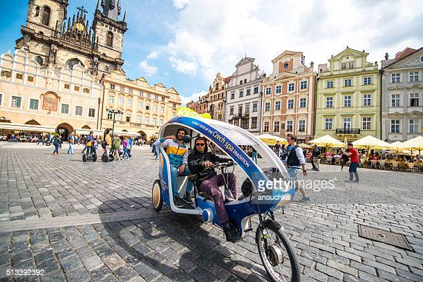 Velotaxi Rickshaw with tourists on Prague Old town square