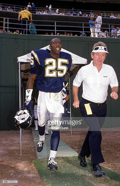 Vencie Glenn of the San Diego Chargers walks out to the field with a staff member during a 1988 NFL season game at Jack Murphy Stadium in San Diego...