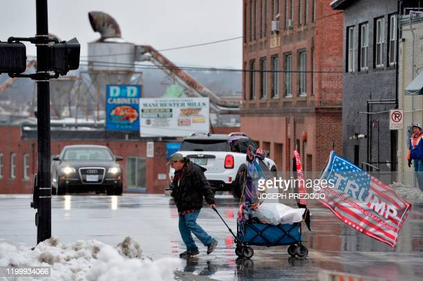 A vender hauls a cart of US President Donald Trump merchandise in the rain hours ahead of President Trump's rally in Manchester New Hampshire on...