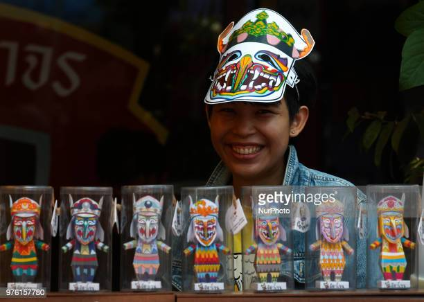 A vender wear a mask representing the spirits of the dead springing back to life as she waits customers during the annual Phi Ta Khon or Ghost...