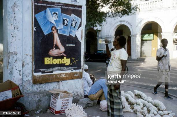 Vendeur de coraux devant une affiche du film 'Blondy' de Sergio Gobbi, dans une rue de Djibouti, en mars 1977.