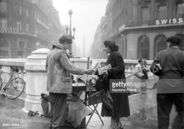 Vendeur de muguet à la sortie du métro Pace de l'Opéra à Paris France en 1951