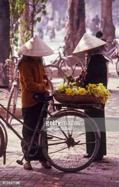 Vendeuses de fleurs a velo a Hanoi Viet Nam