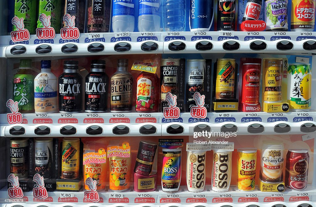 A vending machine along a sidewalk in Tokyo offers a variety of canned and bottled beverages.