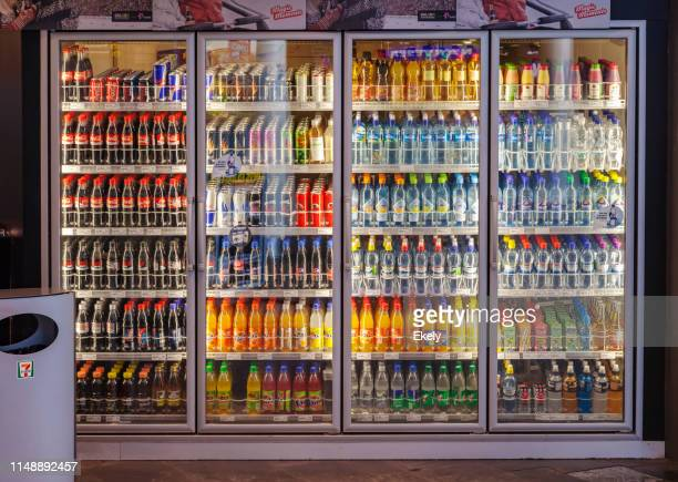 vending machine with lass cabinets showing diverse range of softdrinks.  refrigerator, screen door, soda, drink, bottle - cooling rack stock photos and pictures