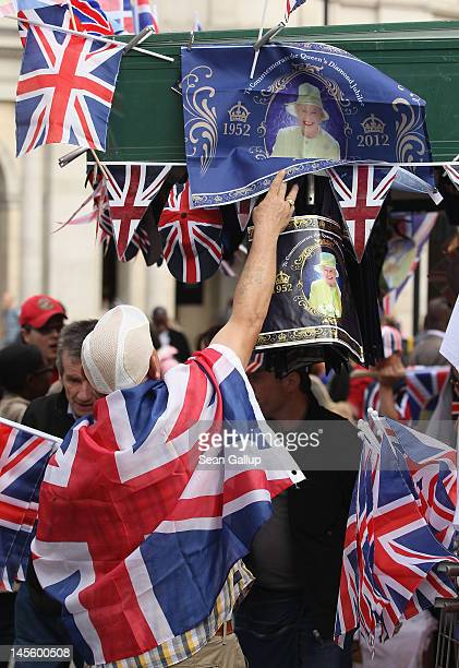 A vendor adjusts souvenir flags commemorating the Diamond Jubilee of Queen Elizabeth II at Trafalgar Square on June 2 2012 in London England For only...