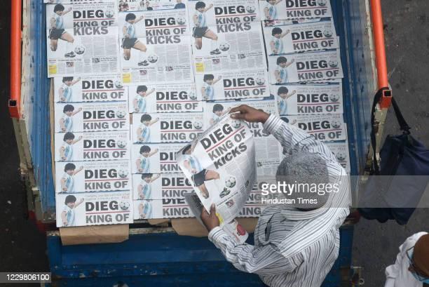 Vendor arrange newspaper seen picture of footballer Diego Maradona who died yesterday at Ultadanga crossing on November 26, 2020 in Kolkata, India....
