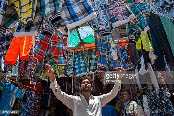 A vendor arranges an overhead display of menswear clothing at a market in Karachi Pakistan on Thursday May 28 2015 Pakistan's budget is scheduled to...
