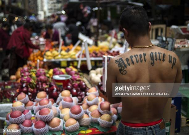A vendor arranges apples at his stall in the crowded Chun Yeung street market in Hong Kong on February 15 as people shop the day before the start of...