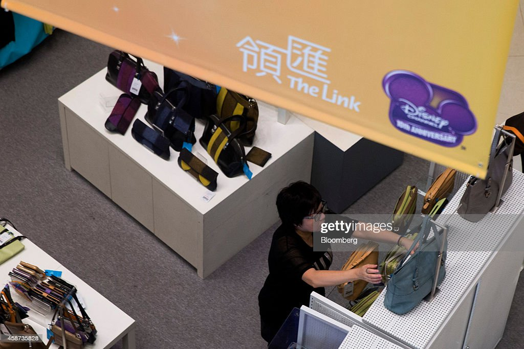 A vendor arranges bags inside a store at Lok Fu Plaza, operated by the Link Real Estate Investment Trust (REIT), in Hong Kong, China, on Monday, Nov. 10, 2014. The Link REIT, Asia's largest property trust which owns neighborhood malls, food markets, and car parks, is scheduled to announce interim results on Nov. 13. Photographer: Brent Lewin/Bloomberg via Getty Images