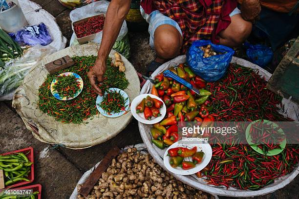 A vendor arranges chill peppers and ginger for sale at a stall in the market district of Divisoria in Manila the Philippines on Monday Jan 6 2014...